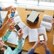 Students with smartphones making cheat sheets — Stock Photo #74724089