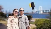 Happy girls with smartphone selfie stick in tokyo — Stock Photo
