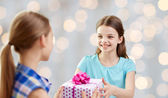 Happy girls with birthday present over lights — Stock Photo