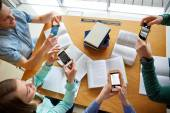 Students with smartphones making cheat sheets — Stock Photo