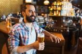 Happy man drinking beer at bar or pub — Stockfoto