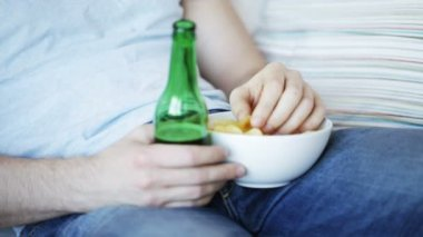 Close up of man eating chips and drinking beer — 图库视频影像