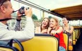 Laughing friends with camera traveling by tour bus — Stock Photo