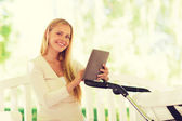 Happy mother with tablet pc and stroller in park — Stock Photo