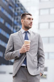 Young serious businessman with paper cup outdoors — 图库照片