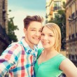 Smiling couple with smartphone in city background — Stock Photo #75201577