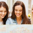 Beautiful girls looking into tourist map in city — Stock Photo #75203175