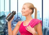Happy woman drinking water from bottle in gym — Foto Stock