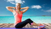 Smiling woman doing sit-up on mat over sea — Stock Photo