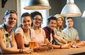 Happy friends drinking beer and cocktails at bar — Stock Photo