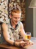 Счастливый человек со смартфона, пить пиво в баре — Стоковое фото