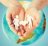 Human hands holding paper couple over earth globe — Stockfoto
