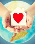 Human hands holding paper house with red heart — Stockfoto
