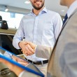 Happy man shaking hands in auto show or salon — Stock Photo #75504023