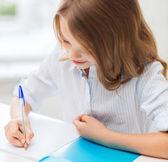 女学生在学校里的笔记本中写 — 图库照片