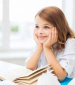 Student girl writing in notebook at school — Stock Photo