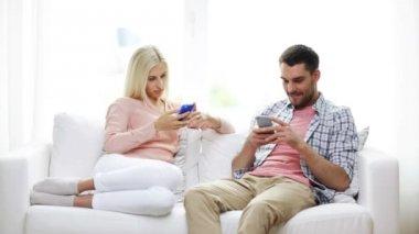 Koppel met smartphones texting thuis — Stockvideo