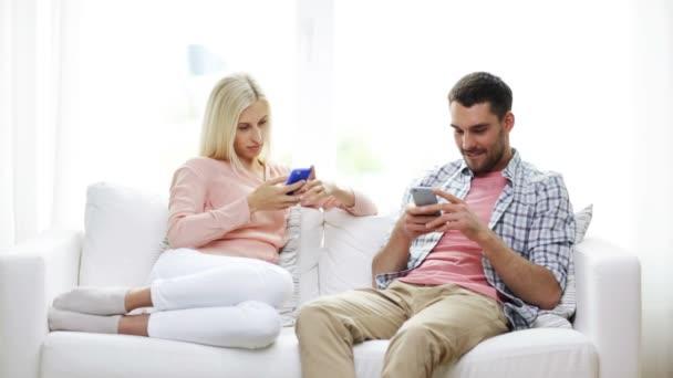 Pareja con smartphones enviar mensajes de texto en casa — Vídeo de stock