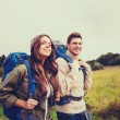 Smiling couple with backpacks hiking — Stock Photo #75718673