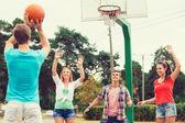 Group of smiling teenagers playing basketball — Stockfoto