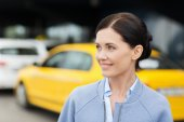 Smiling woman over taxi station or city street — Stock Photo