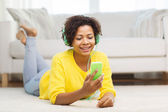 Happy african woman with smartphone and headphones — Stock Photo