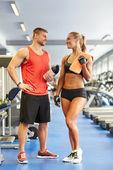 Glimlachende man en vrouw praten in de sportschool — Stockfoto