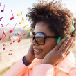 Happy young woman in headphones listening to music — Stock Photo #75807037