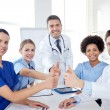 Group of doctors showing thumbs up at hospital — Stock Photo #75807261
