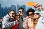 Smiling friends taking selfie with smartphone — Stock Photo
