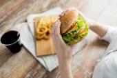 Close up of woman hands holding hamburger — Stock Photo