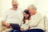 Smiling family with tablet pc at home — Stock Photo