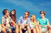 Group of smiling friends sitting on city street — Stock Photo