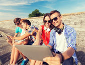 Group of smiling friends with tablet pc outdoors — Stock Photo