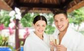 Happy couple in bathrobes with champagne at resort — Stock Photo