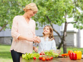 Happy family cooking vegetable salad for dinner — Stock Photo