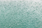 Water surface with raindrops at rainy day — Stock Photo