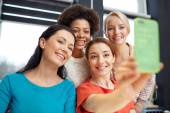 Happy young women taking selfie with smartphone — Stock Photo