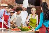 Happy friends and chef cook cooking in kitchen — Stock Photo