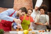 Happy friends and chef cook baking in kitchen — Stock Photo