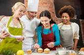 Happy women and chef cook baking in kitchen — Stock Photo