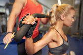 Man and woman flexing muscles on gym machine — Stock Photo