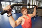 Man flexing muscles on cable machine gym — Stock Photo