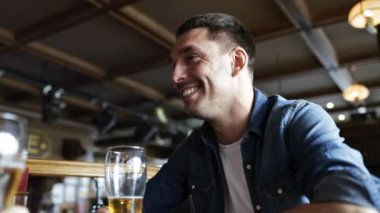 Happy young man drinking beer at bar or pub — Stock Video