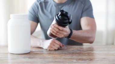 Close up of man with protein shake bottle and jar — Stock Video