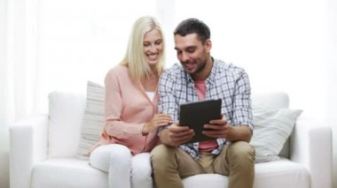 Happy couple with tablet pc at home — Wideo stockowe