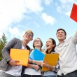 Group of happy students with folders outdoors — Stock Photo #76468435