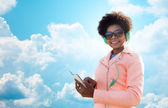 Happy young woman with smartphone and headphones — Stock Photo