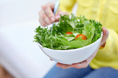 Close up of young woman eating salad at home — Stock Photo