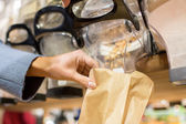 Close up of hand pouring nuts to paper bag — Stock Photo